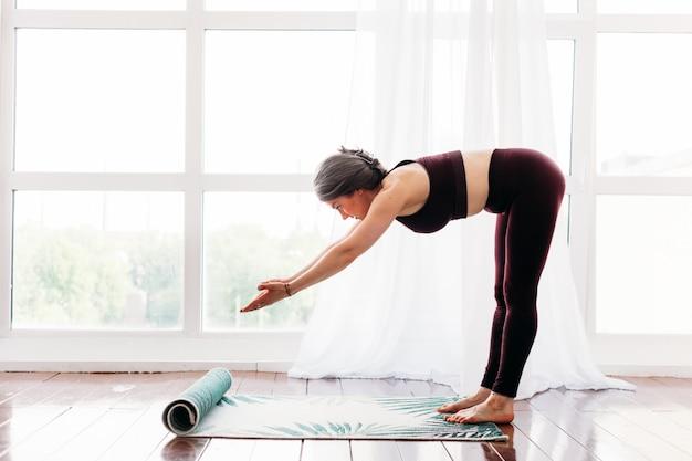 Garota faz exercícios, alongamento, ioga, perto da janela, roupa de ioga, corpo, magreza e saúde, espalhamos um tapete de ioga, aulas em casa