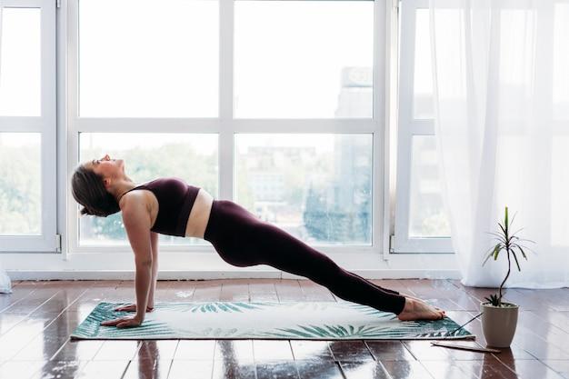 Garota faz exercícios, alongamento, ioga, perto da janela, roupa de ioga, corpo, magreza e saúde
