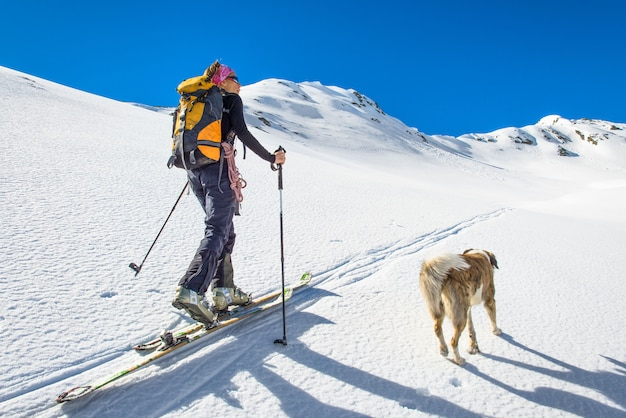 Garota faz montanhismo de esqui com cachorro.