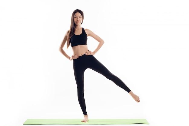 Garota faz o exercício de retirar as pernas para o lado.