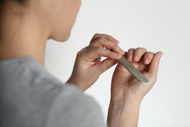 Garota faz procedimento profissional de manicure. fechem as mãos.