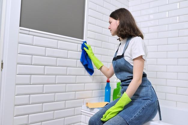 Garota fazendo a limpeza no banheiro. adolescente em luvas de avental com detergente e pano de lavagem de parede de azulejos brancos, copie o espaço. limpeza, limpeza em casa, serviço, jovens