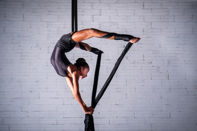 Garota fazendo acrobacias aéreas em sedas