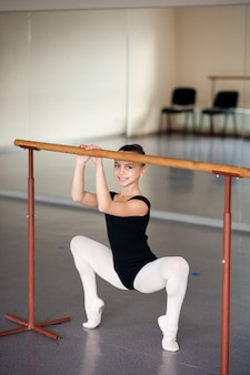 Garota fazendo alongamento na escola de balé.
