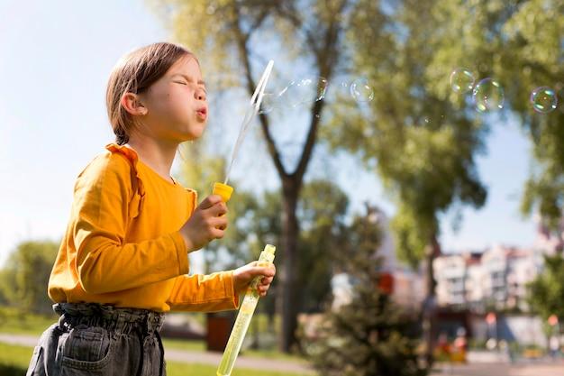 Garota fazendo bolhas de sabão tiro médio