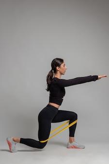 Garota fazendo estocadas com banda de resistência na parede cinza