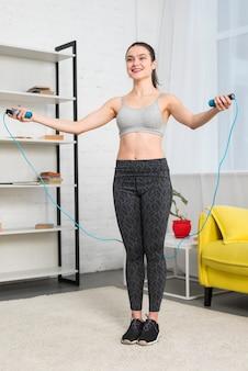 Garota fazendo exercício com pular corda em sua casa