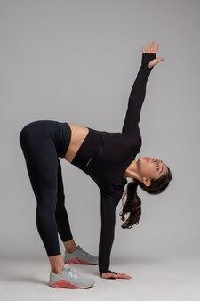 Garota fazendo exercícios de alongamento contra uma parede cinza