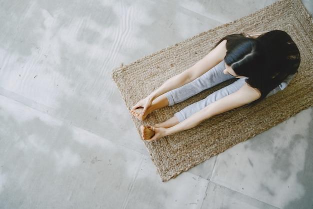 Garota fazendo exercícios de ioga em casa perto do sofá e da janela em roupas esportivas