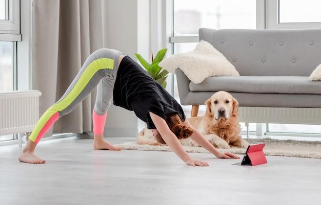 Garota fazendo exercícios de ioga online com tablet em casa em época de pandemia e cachorro retriever dourado olhando para ela