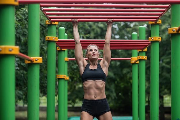 Garota fazendo exercícios na barra horizontal, a mulher está envolvida em exercícios