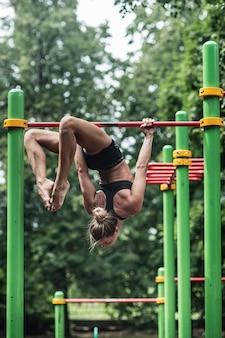 Garota fazendo exercícios na barra horizontal. a mulher está envolvida em exercícios