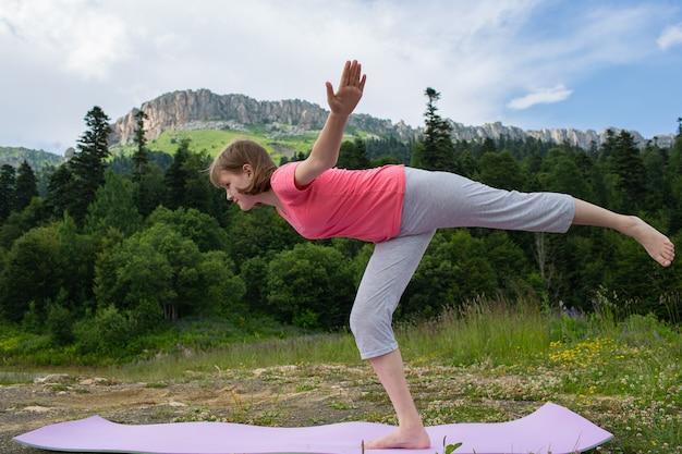 Garota fazendo ioga na natureza em um fundo de montanhas