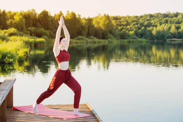 Garota fazendo ioga no cais de madeira perto do lago no verão