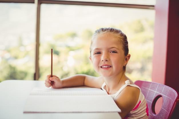 Garota fazendo lição de casa em sala de aula