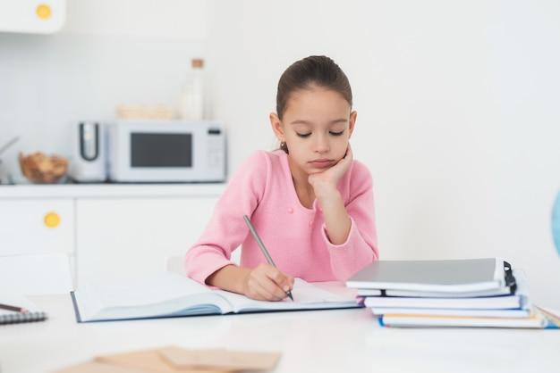 Garota fazendo lição de casa na cozinha.