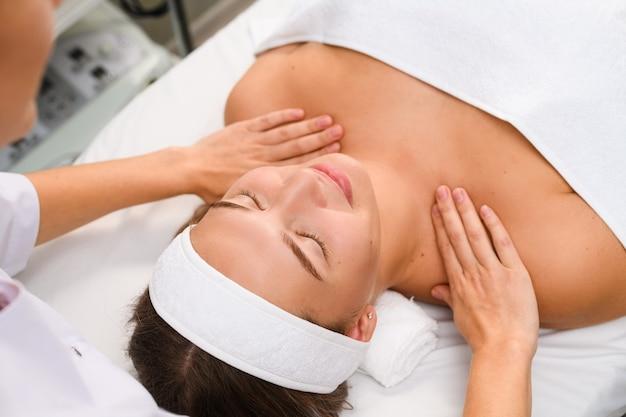 Garota fazendo massagem nas mãos da clavícula e ombros em clínica de salão de beleza