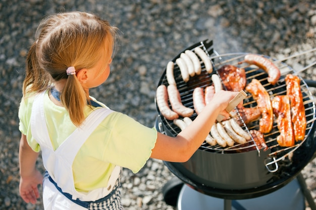 Garota fazendo o churrasco