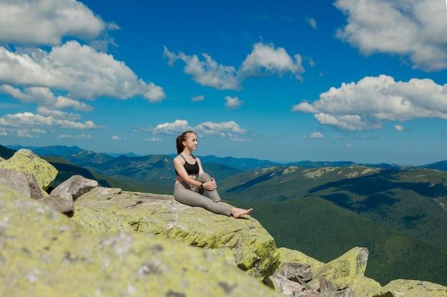 Garota fazendo pose de lótus de exercícios de ioga no topo da montanha.