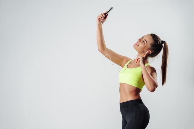 Garota fazendo selfie em pé frente a câmera sobre fundo cinza