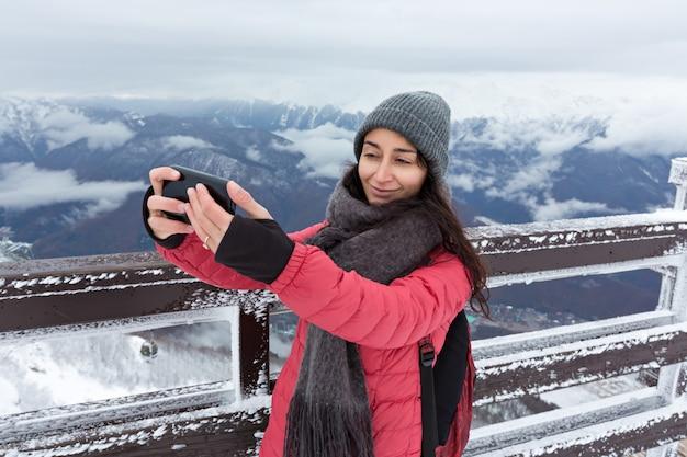Garota fazendo selfie nas montanhas no inverno