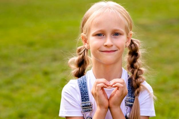 Garota fazendo um coração com as mãos