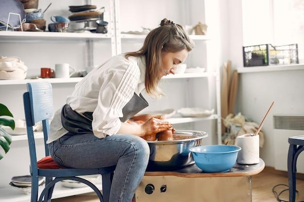 Garota fazendo um vaze de barro na máquina de uma cerâmica