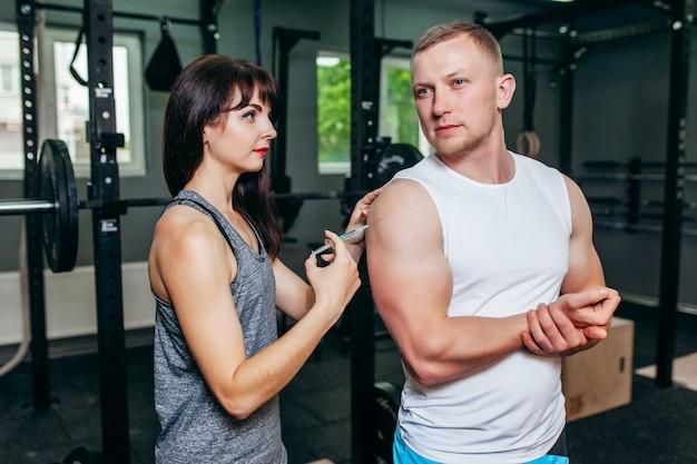 Garota fazendo uma injeção no namorado na academia