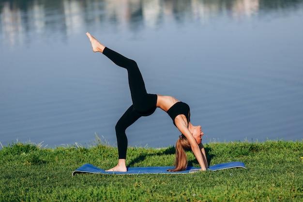 Garota fazendo yoga asana em pé nas mãos dela durante a curva para trás. um atraso
