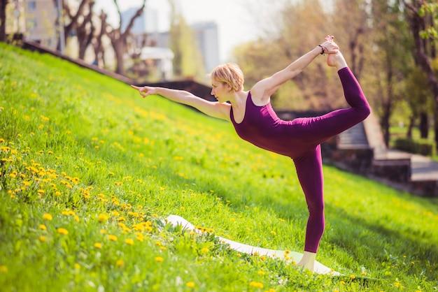 Garota fazendo yoga na grama verde em um dia ensolarado