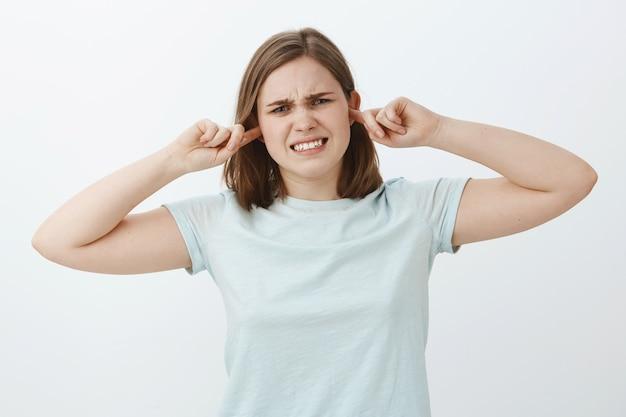 Garota fecha os ouvidos e se sente descontente quando as pessoas brigam perto dela. mulher jovem e intensa, insatisfeita, cerrando os dentes por causa da sensação de desconforto incomodada pelo som alto cobrindo a audição com tampões de ouvido