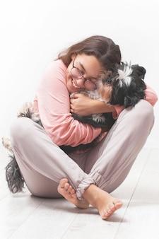 Garota feliz abraça o cachorro dela.