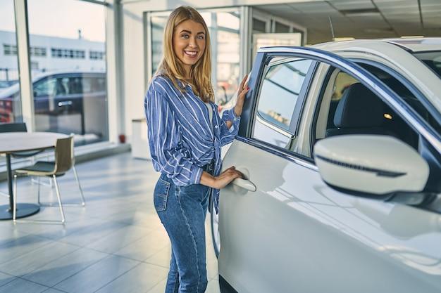 Garota feliz abrindo a porta do carro no showroom de carros