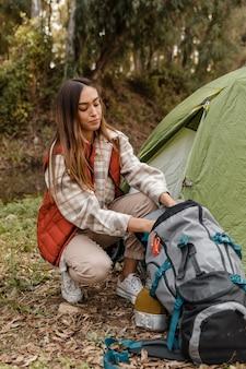 Garota feliz acampando na floresta fazendo as malas