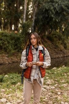 Garota feliz acampando na floresta segurando um telefone celular