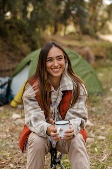Garota feliz acampando na floresta sorrindo