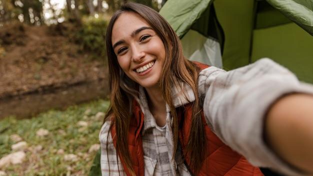 Garota feliz acampando na floresta tirando uma foto de si mesma