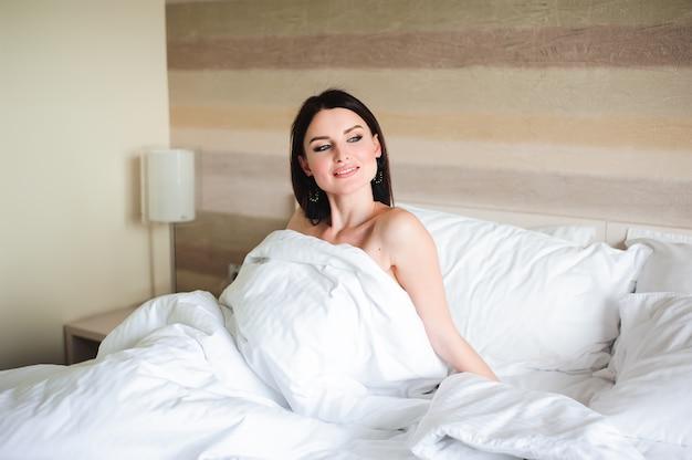 Garota feliz acordando esticando os braços em cima da cama de manhã.