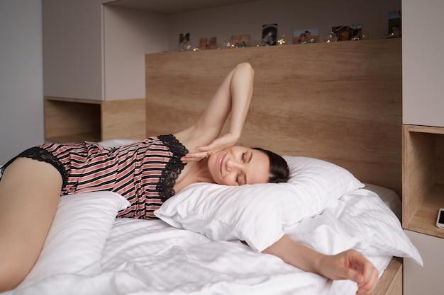 Garota feliz acordando esticando os braços na cama pela manhã