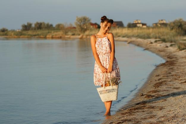 Garota feliz ao pôr do sol à beira-mar com um saco de palha e um chapéu fica com os pés descalços. o fundo está desfocado.