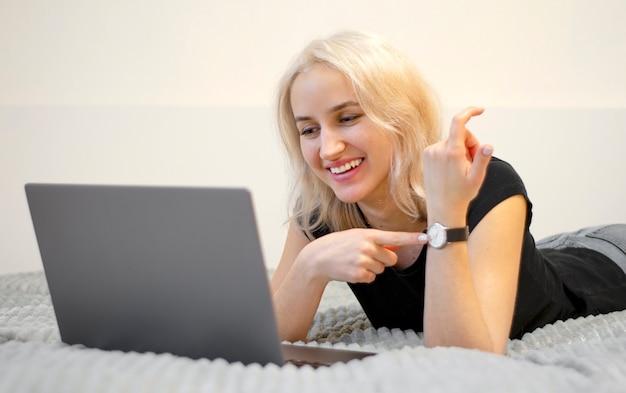 Garota feliz aponta para o relógio. o valor do tempo. negócios na internet. veio para a reunião na hora certa.