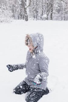 Garota feliz, aproveitando a queda de neve na floresta no inverno