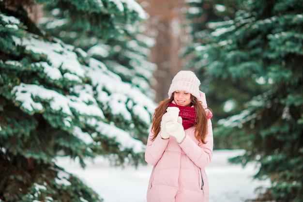 Garota feliz aproveite o clima de inverno e neve ao ar livre no belo dia de wonter