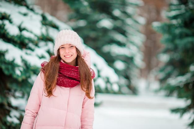 Garota feliz aproveite winer e neve clima ao ar livre no belo dia de wonter