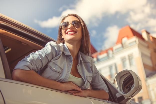 Garota feliz atraente em roupas elegantes e óculos de sol.