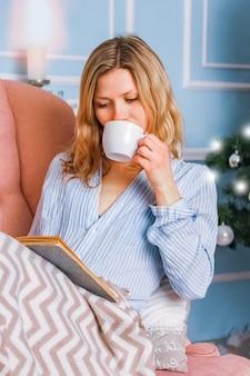 Garota feliz bebendo chá de café em casa no natal