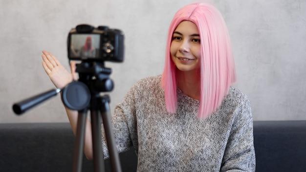 Garota feliz blogueira com peruca rosa na frente da câmera em um tripé