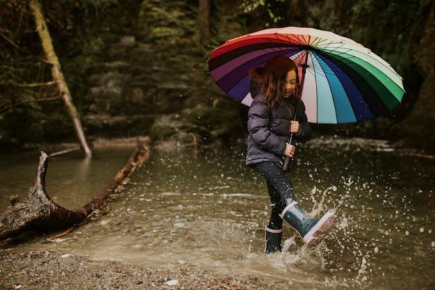 Garota feliz brincando no lago da floresta com um guarda-chuva em um dia chuvoso