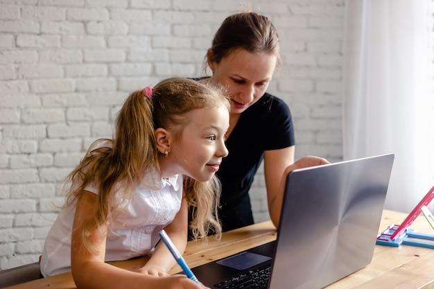 Garota feliz com a mãe estudando online em casa. vírus corona e conceito de quarentena. aprendizagem online ou conceito de tecnologia educacional