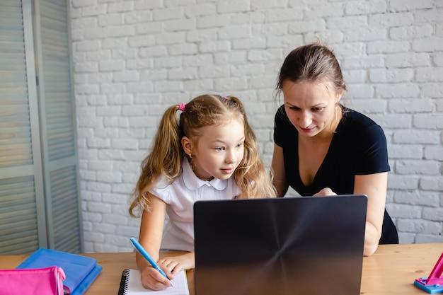 Garota feliz com a mãe estudando online em casa. vírus corona e conceito de quarentena.